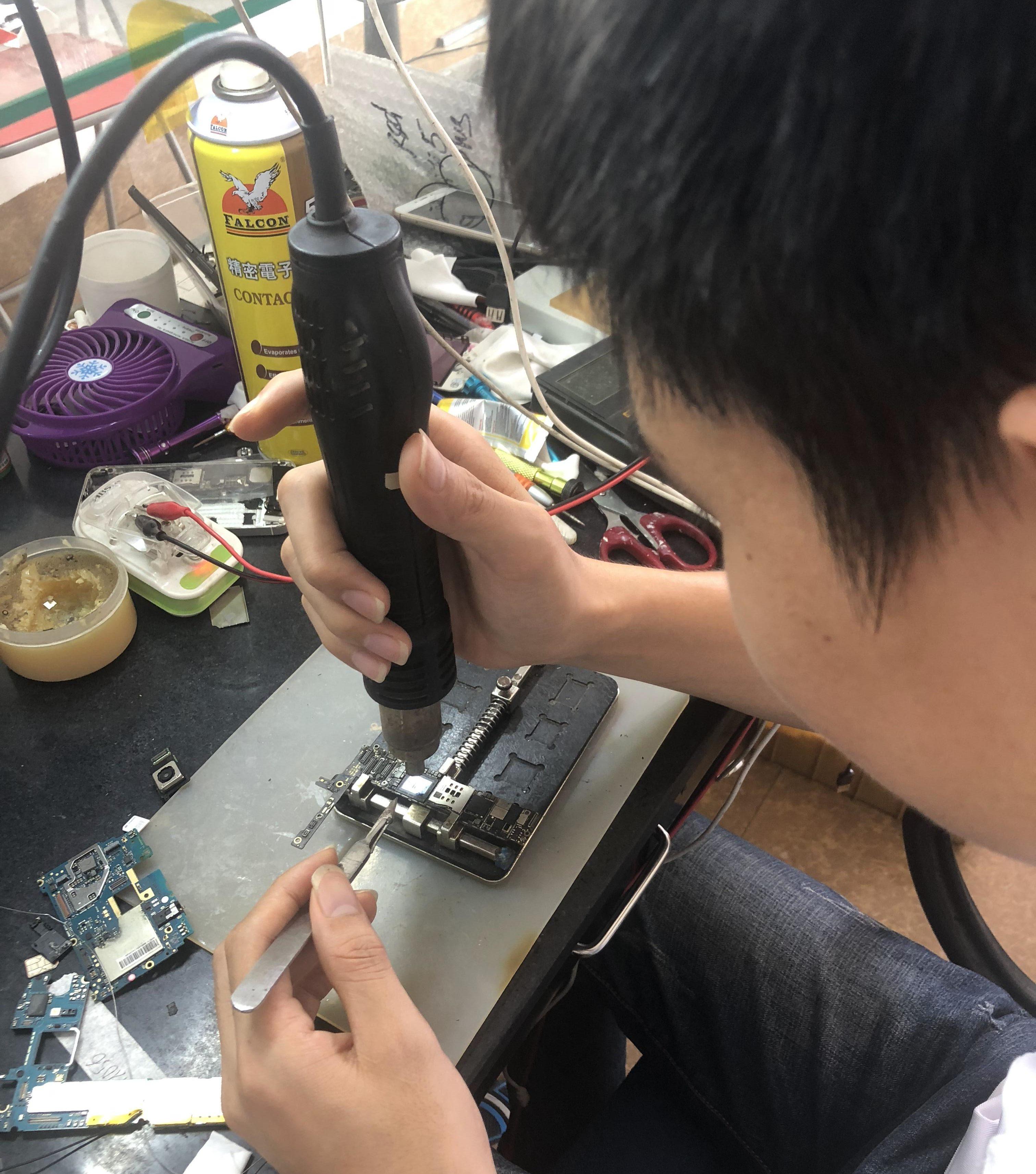 Kỹ thuật viên đang thay mic HTC One Mini