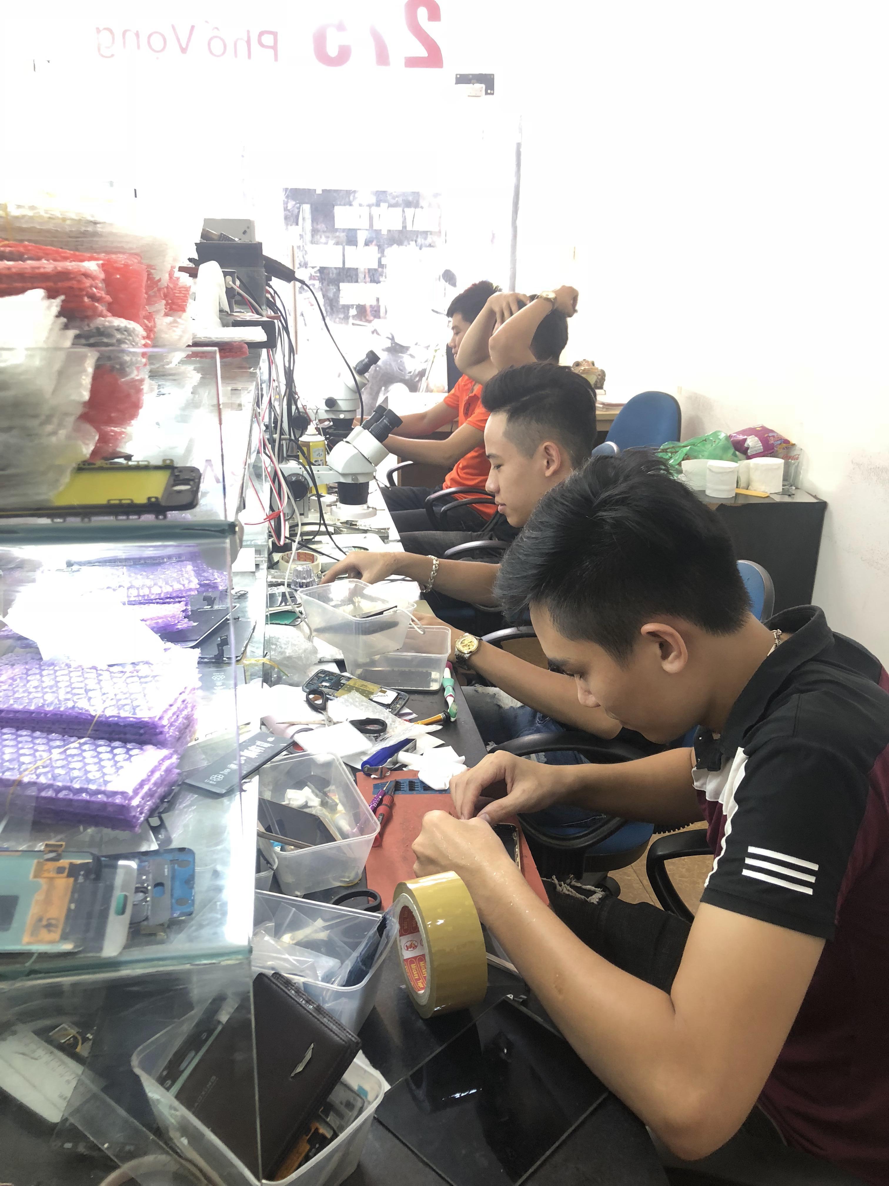 Kỹ thuật viên thay pin điện thoại trực tiếp trước mặt khách hàng.